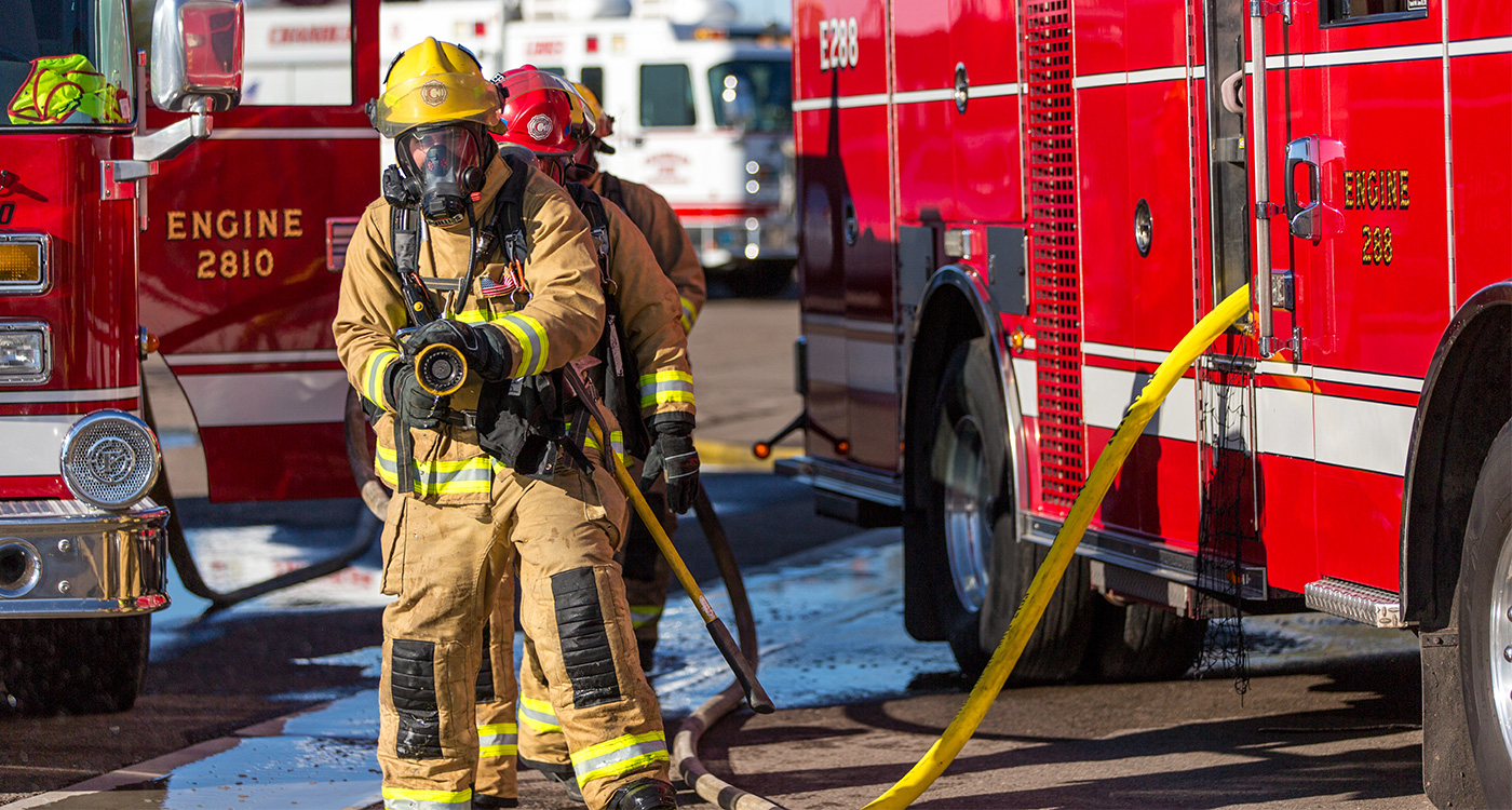 A Chandler firefighter with hose in hand ready for a training drill