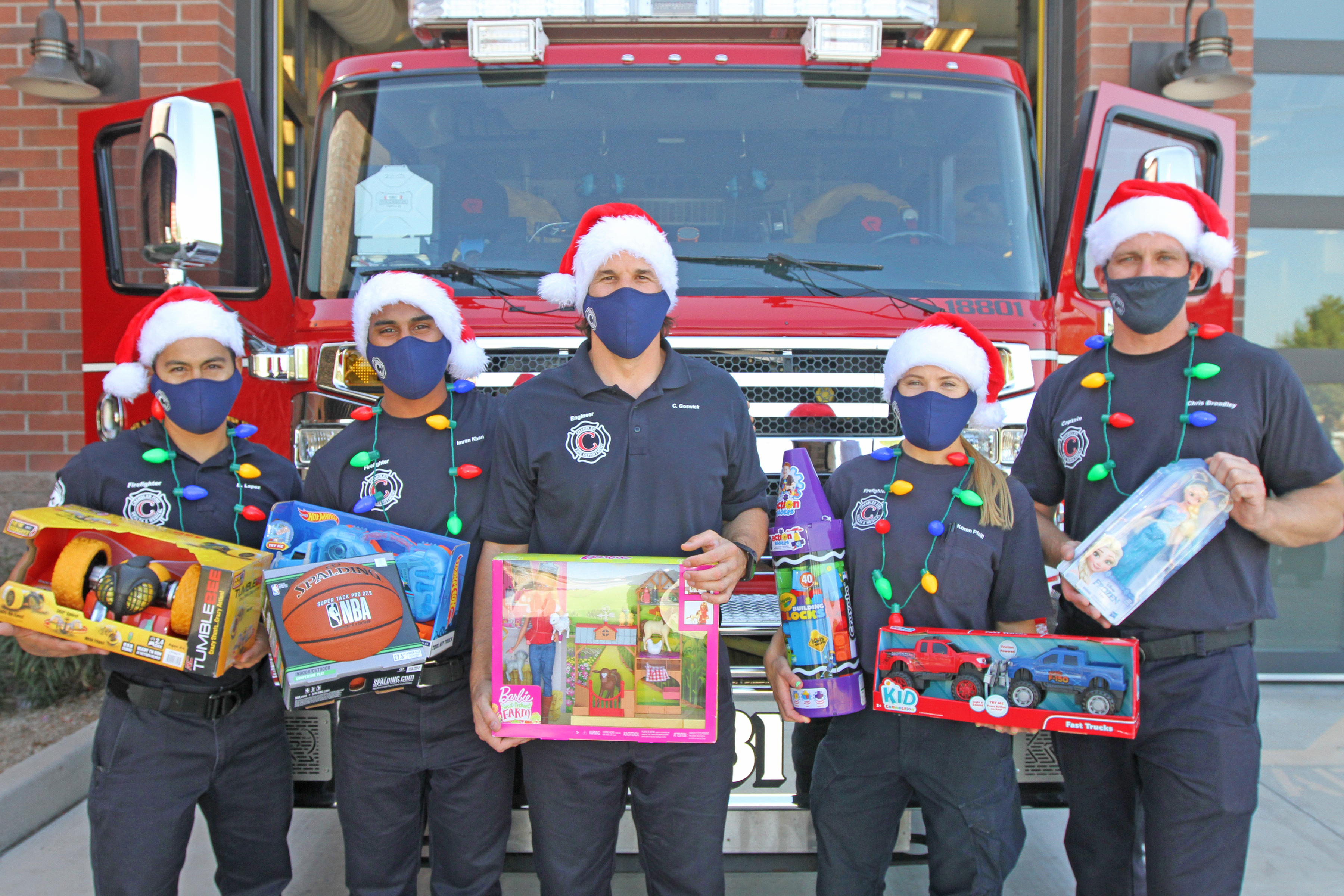 Chandler Firefighters hold toys in front of a firetruck.