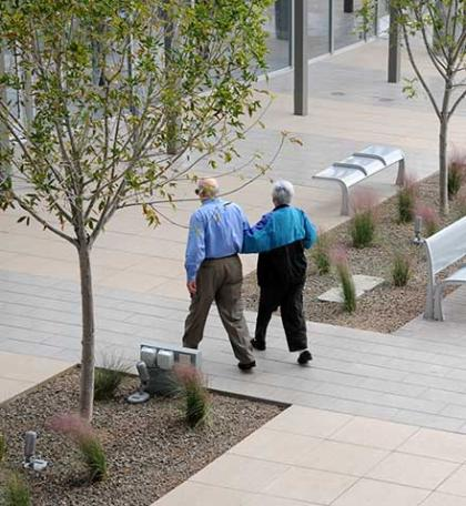 Elderly couple walking through City Hall courtyard