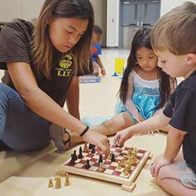 L.I.T. participant playing chess with kids