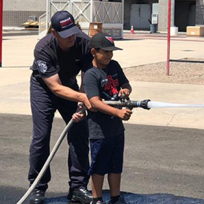 Chandler firefighter showing a child how to operate a fire hose
