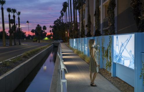Woman overlooking the Commonwealth Canal in Downtown Chandler at sunset