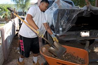 Resident using a shovel and wheelbarrow as part of the Neighborhood Cleanup Program