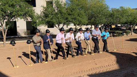 Laser Components Management shoveling dirt at groundbreaking event