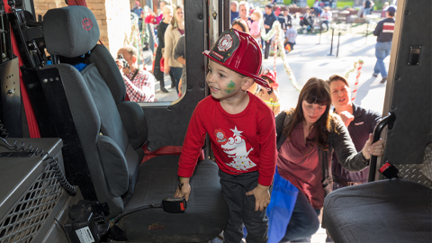 Young boy on fire truck at Holiday Toy Ride
