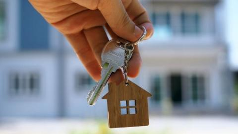 "Photo of person holding a key with a ""home"" keychain"