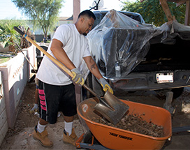 A resident shoveling dirt into a wheelbarrow